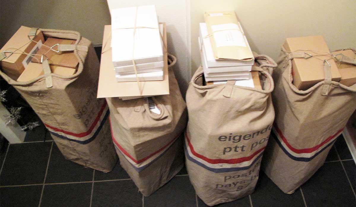 Pakketjes van de webwinkel in postzakken van PostNL.